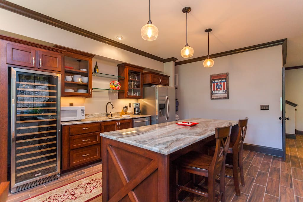 Open kitchen with modern lighting makes this space a perfect hangout.  Includes custom cherry cabinets, granite, copper sink, and stainless steel appliances.  Includes everything except oven/stove.