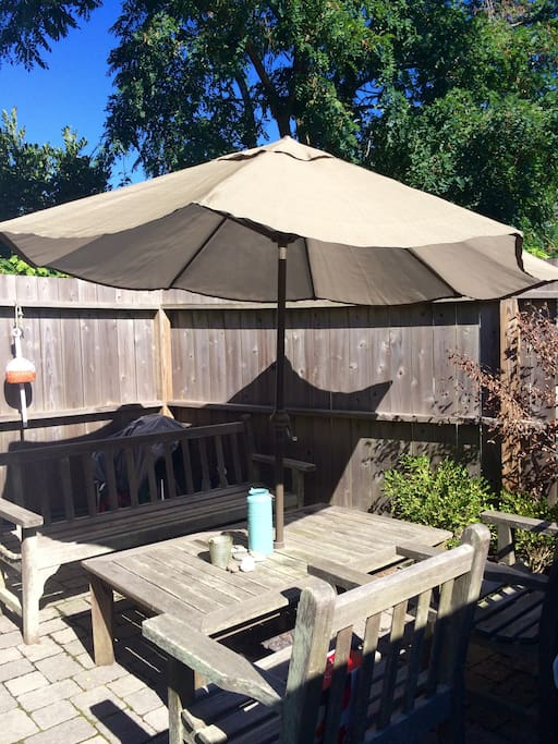 Backyard enclosed patio area with grill and large umbrella for shade perfect for entertaining