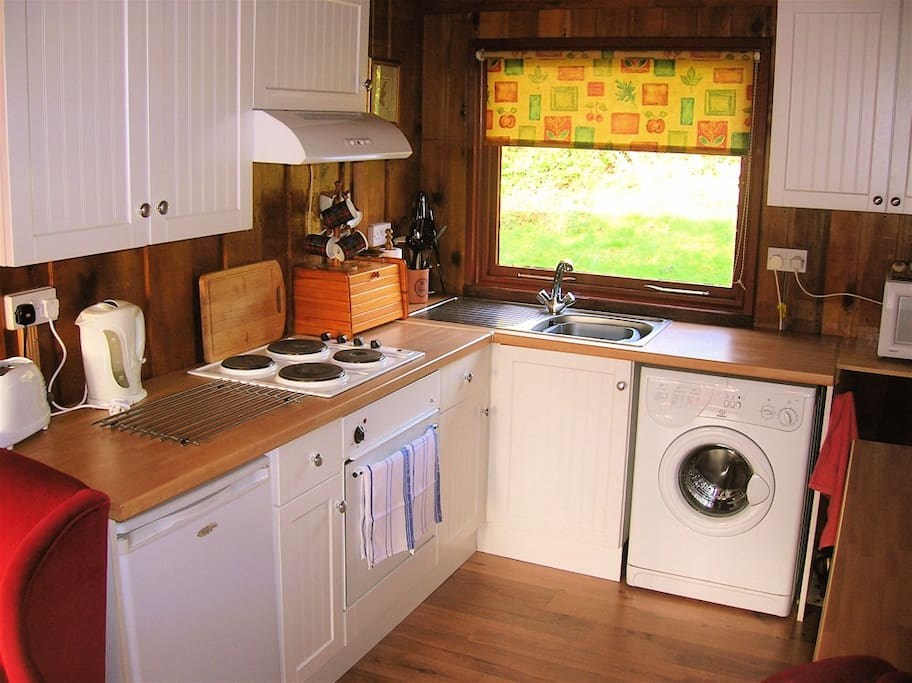 Neat and well equipped modern units in kitchen: fridge, microwave, oven, sink washing machine and hob