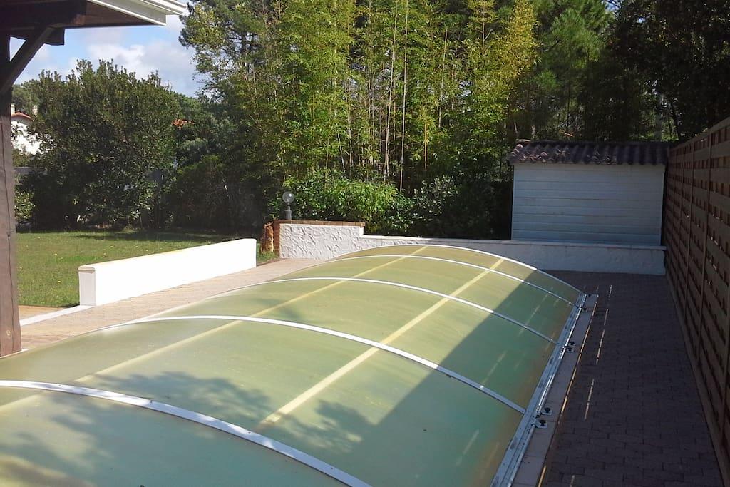 La piscine avec sa protection amovible située côté sud ouest de la villa