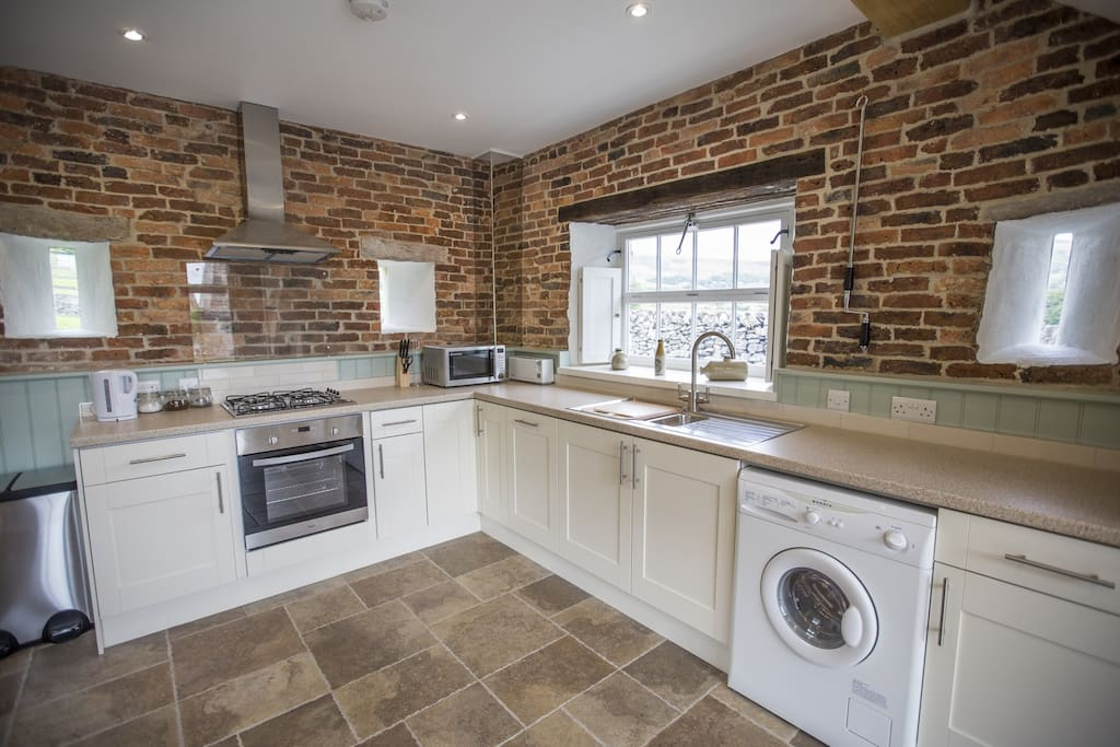 The fully fitted kitchen includes views over hills and fields.