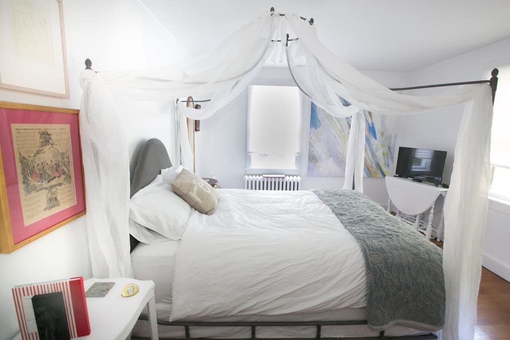 The Rosie Bedroom has a Queen-sized canopy bed and cozy chaise lounge