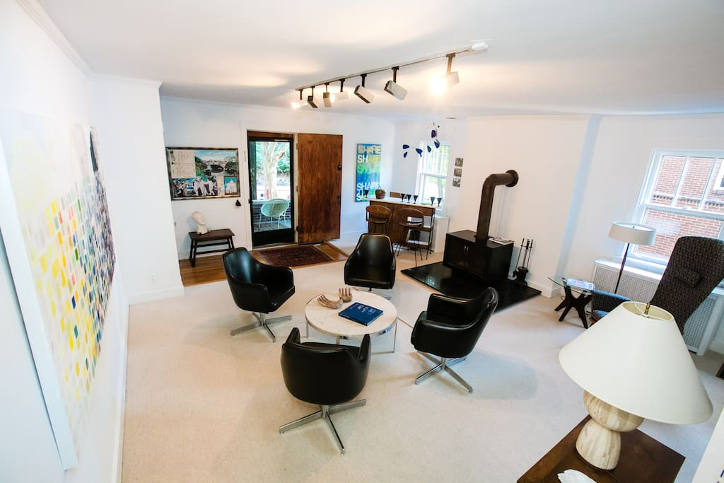 """Lounge style living area with wood burning fireplace and a tiki bar, sleeper sofa and 50"""" flat screen TV"""