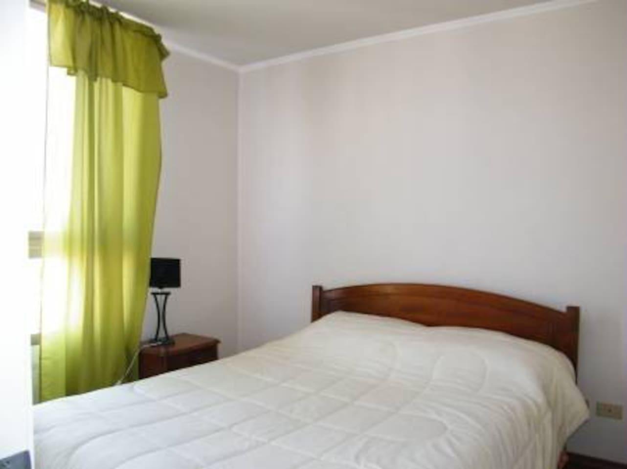 Habitación con cama dos plazas y baño en suite.