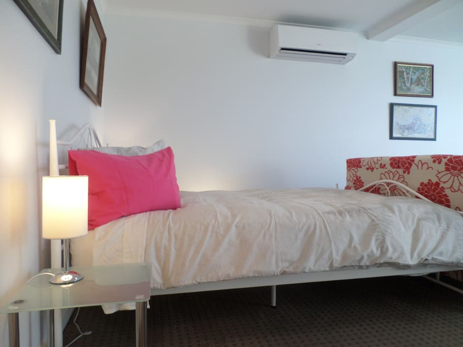 Comfortable queen size bed with reverse cycle air conditioner above bed on wall.