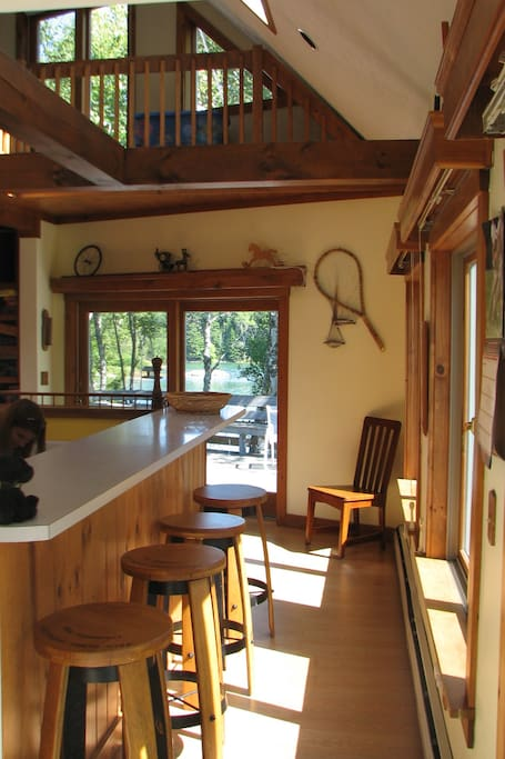 The bar overlooking the kitchen. Straight ahead is the dining table with views of the water.