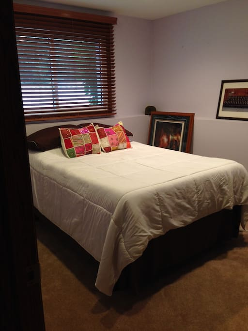 Carpeted room with comfy queen bed.