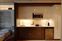 The kitchen boasts an induction stove, convection microwave, built-in dishwasher, and a Nespresso machine, with complementary capsules.