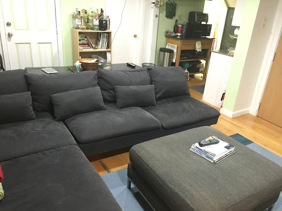 "Living room with sectional couch, cable TV, and 60"" projection screen. Couch can comfortably sleep 2 extra people if necessary."