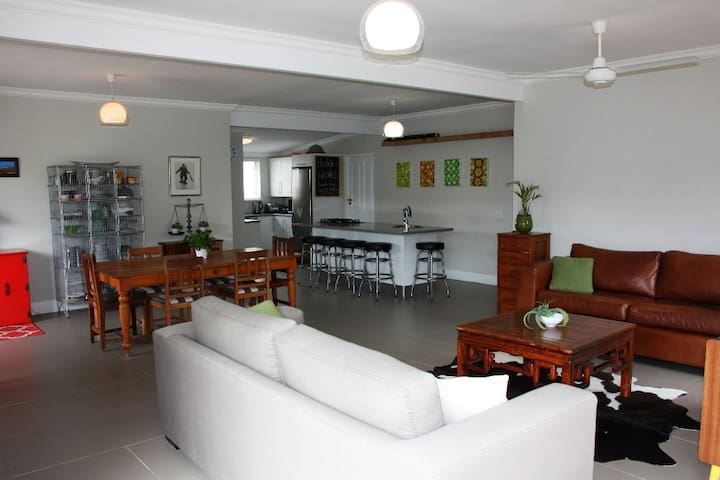Open plan living kitchen area that looks out onto the braai area and garden