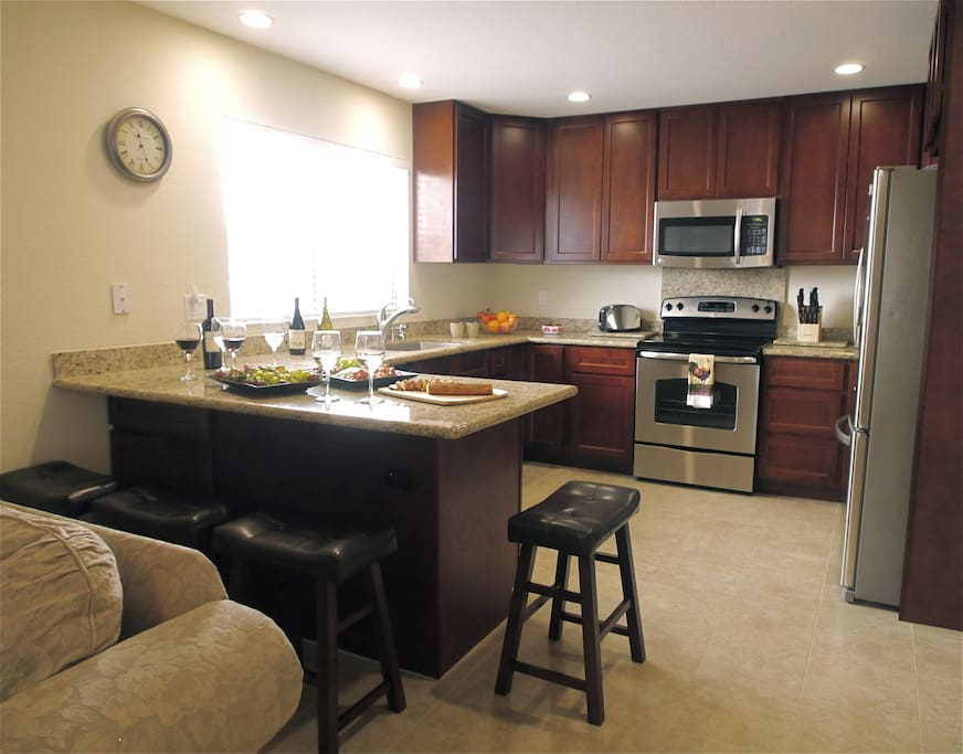 This Open Kitchen Features Stainless Steel Appliances & Granite Countertops