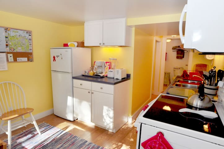 Fully equipped kitchen leading to small laundry room and bathrom