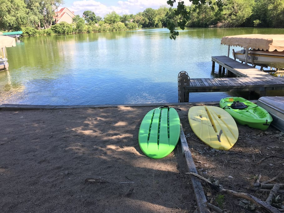 Beach with paddle boards and a kayak ready to use