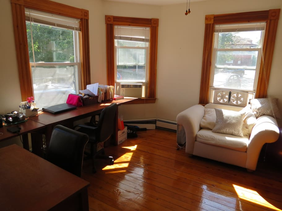 Sun filled living room, comfy chair and desk space.