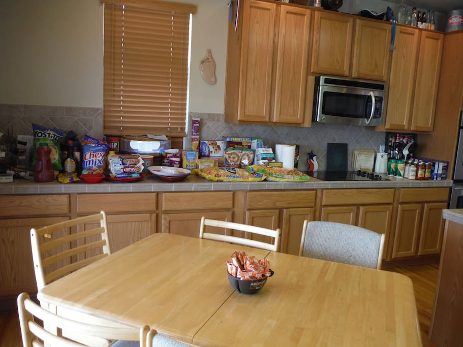 Spacious kitchen has plenty of counter space, double ovens, GE Profile appliances, breakfast bar, and eating area.