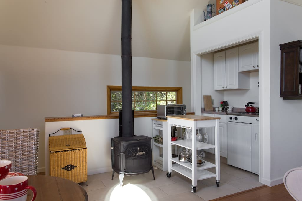 Keep cozy with wood stove; view of kitchen.