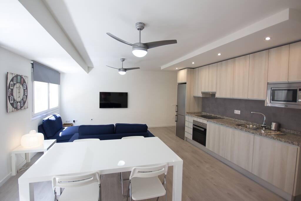 Vista de salón completo -cocina americana de las zonas comunes del piso habitación desde la puerta de acceso de una de las habitaciones del piso.