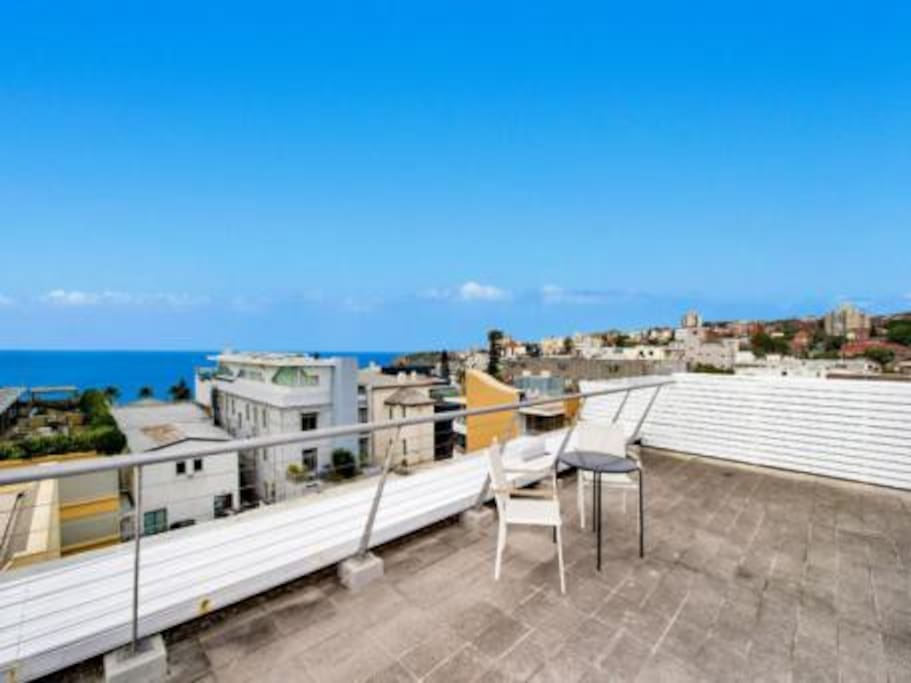 Rooftop with seating and BBQ's and view to the ocean