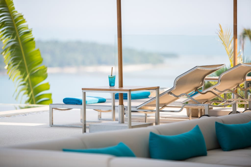 Relax near the pool with a cold drink and a sea view