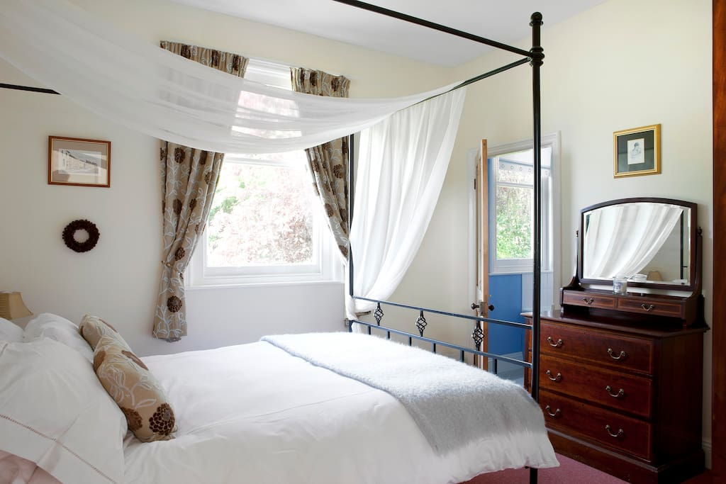 Master bedroom with a four poster bed and king size bed