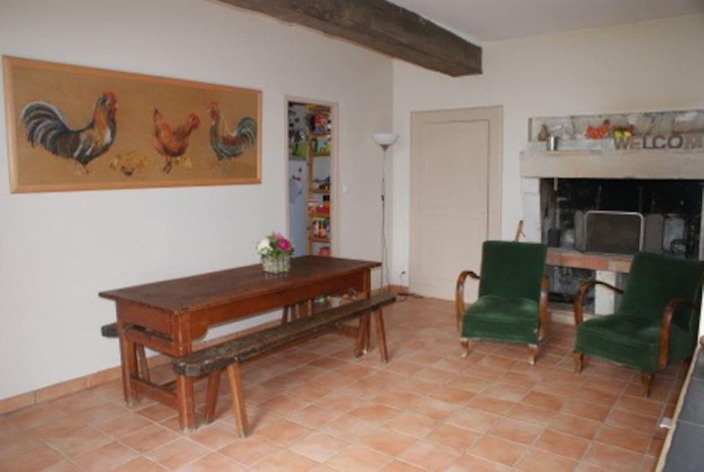 grande salle à manger avec deux très grandes tables familiales et cheminée ouverte. vous apercevez l'arrière cuisine