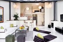 Enorme salón de 40 m2 con suelos de mármol y chimenea. El sofá es convertible en cama doble.