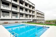 Edificio con jardines y piscina.