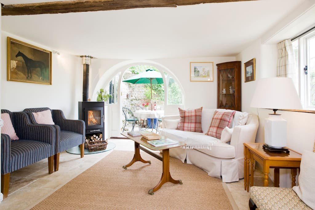 Cosy sitting room with log burning stove and french windows out onto patio