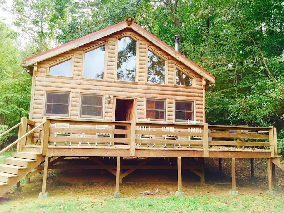 Front of cabin w rocking chairs facing river.