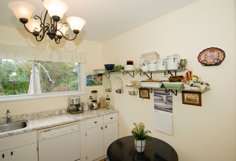 Sunny kitchen with breakfast nook. Fridge and cupboard space. Stove. Espresso machine. Blender.