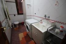 Bagno di servizio con doccia e lavatrice