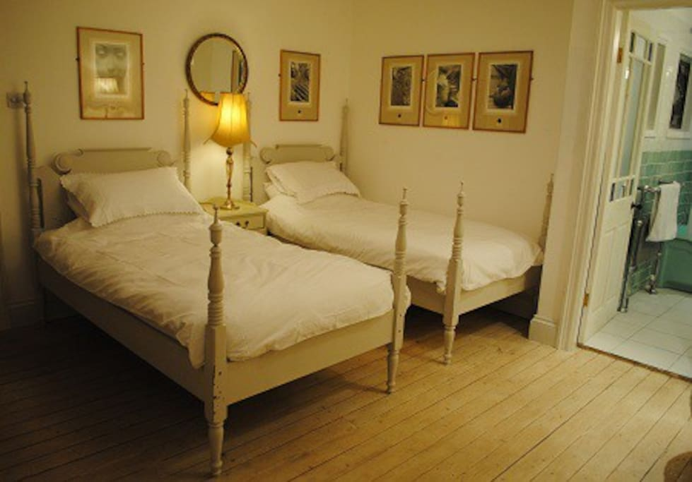 Twin bedroom with ensuite Art Deco bathroom and original artwork on the walls.