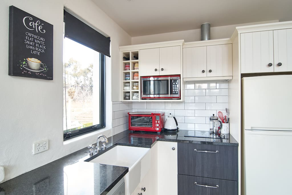 compact kitchen with fridge, microwave, bench-top oven and ceramic cooking elements.