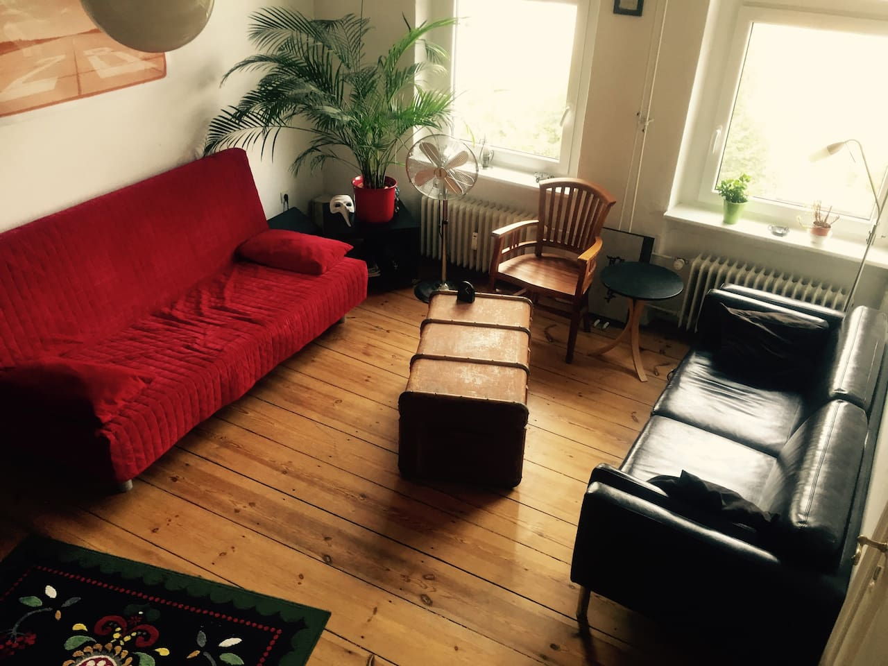 Big and light living room, wooden floor, the red sofa can be a bed for two people