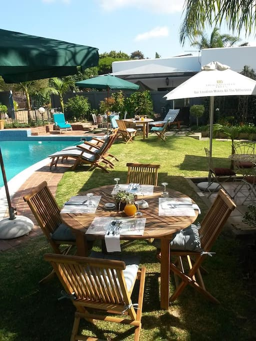 Breakfast tables set in garden area next to pool