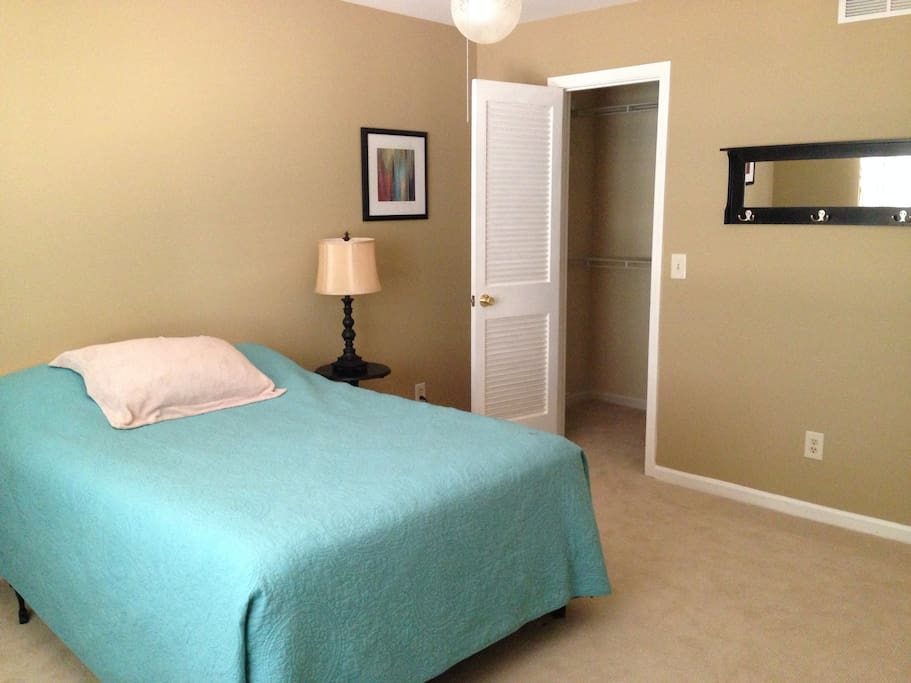 A comfortable and clean room for two with luggage rack and full closet.