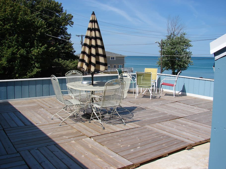 Deck overlooking beach with 2 tables.