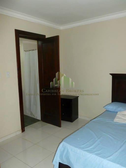 Habitación con su baño, closet, TV  aire acondicionado, ventilador.