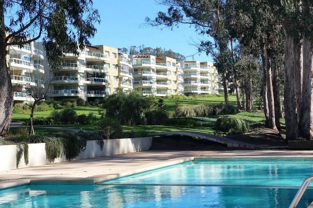Dos complejos de piscinas exteriors rodeados de hermosos jardines.