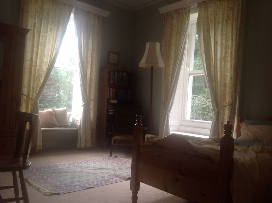 This is the guest's private bedroom. There are two single beds, a desk, chair, armchair and bed side locker.