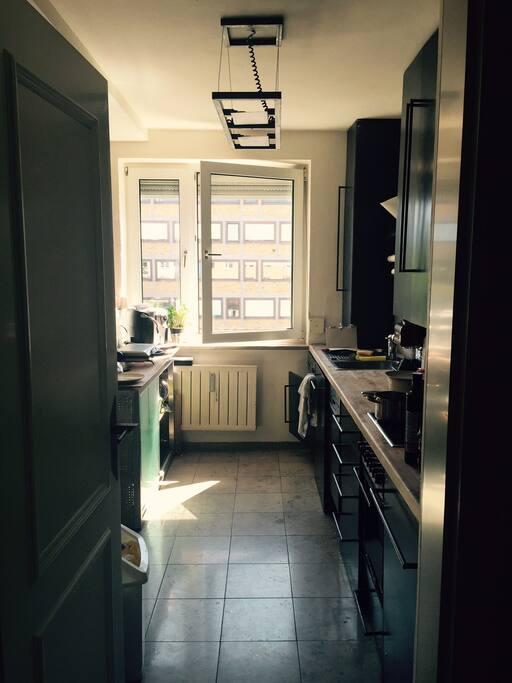 Coole Küche mit allen wichtigen Geräten, wie Kühlschrank, Herd, Spülmaschine und Waschmaschine