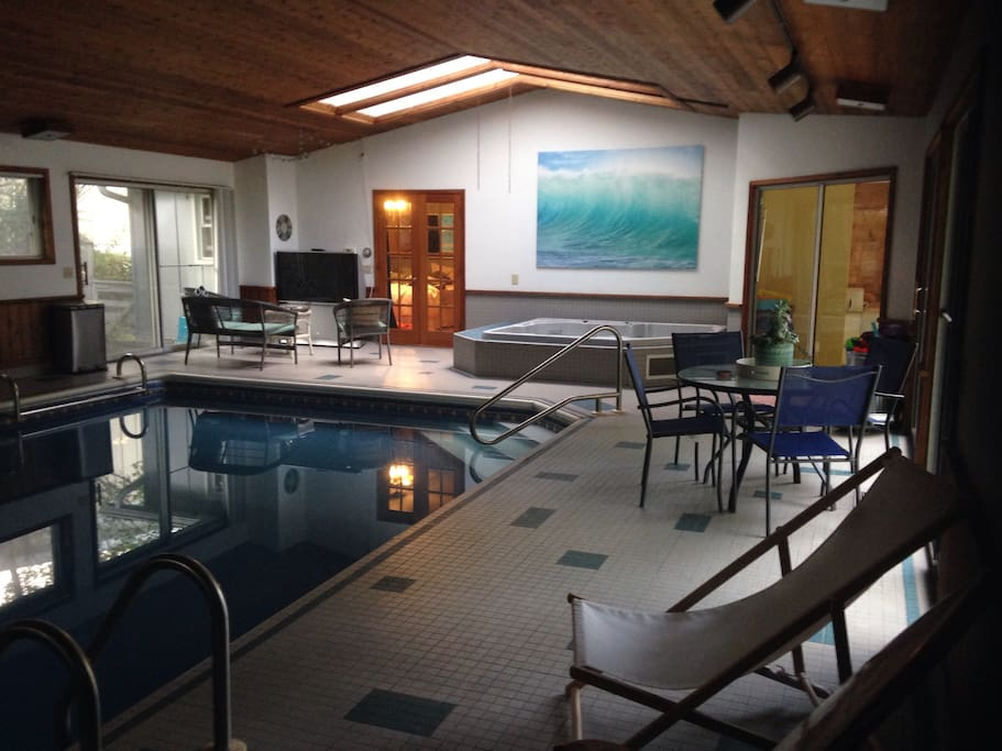 Pool with hot tube and big screen sitting area in pool room