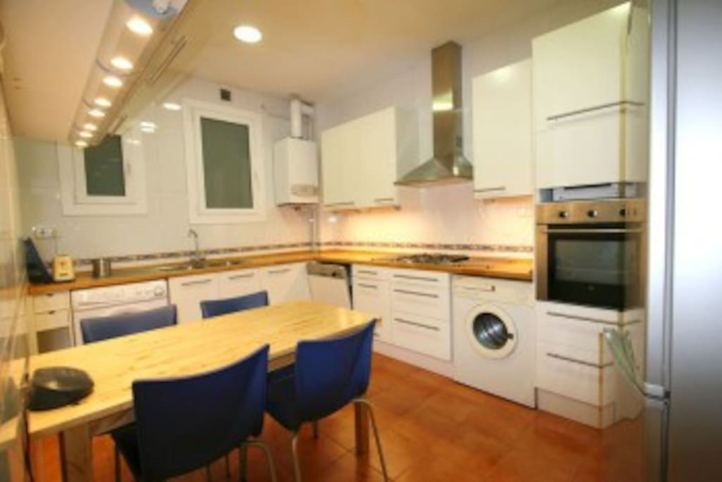 Kitchen with lots of space, dish washer, laundry machine, microwave, oven,  stove, fridge and freezer