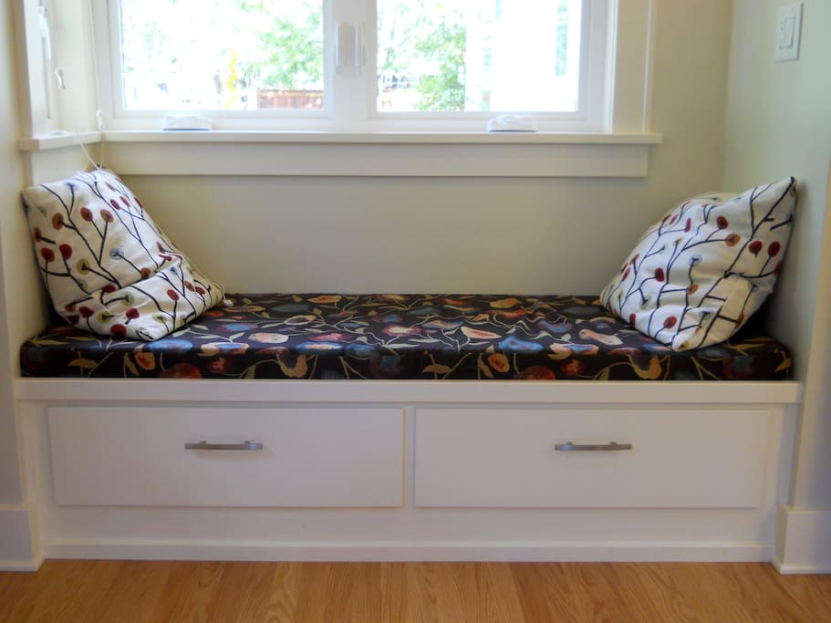 Window seat in  bedroom with drawers underneath.