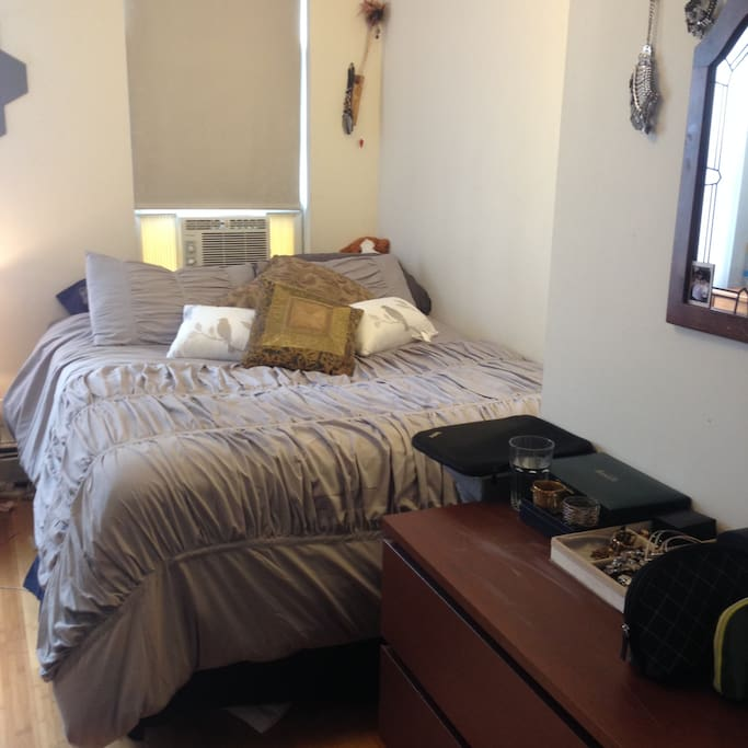 Bedroom has a queen size bed, dresser, desk, two large windows, AC, space heater and two chairs.
