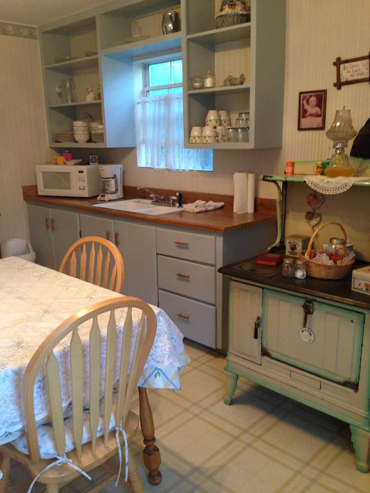 Shared kitchenette with coffee pot, microwave, small fridge and dishes.