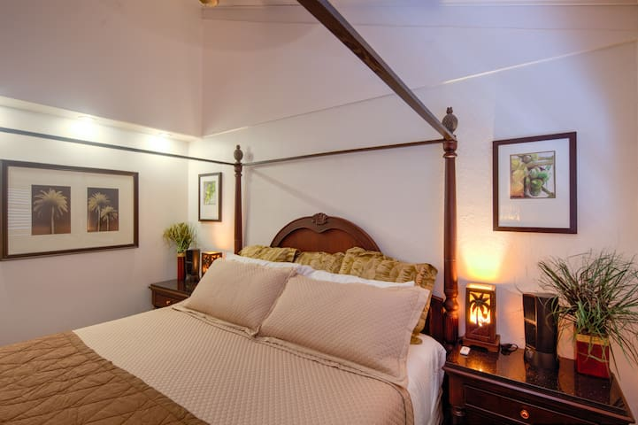 Bedroom has King-size Poster Bed, Side Tables, Palm Tree Lamps, Ceiling Fan under a Vaulted Ceiling