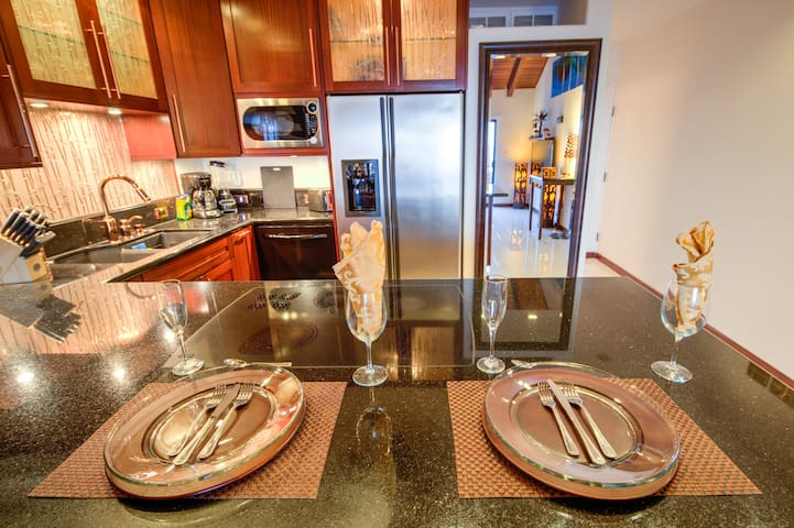 Kitchen with granite countertop with built-in cooktop, stainless steel refrigerator and microwave, blender, coffee maker, toaster, knife block, etc.