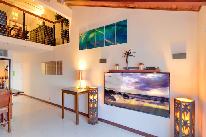 Living Room featuring 70-inch TV, metal wall art, palm tree lamps