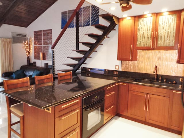 Kitchen Featuring Granite Counters, Cooktop, Stove, custom Mahogany cabinetry